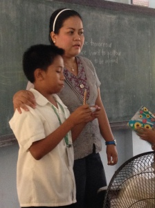 A high school teacher supports a student as he presents.