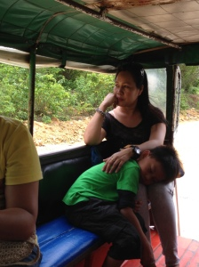 Riding on a Jeepney. They are the size of large vans with two side-facing benches. The open sides have plastic covers that can be pulled down in the rain.